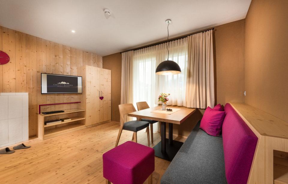 Chalet Rudana - gemütliches Wohnzimmer mit Couch, Lehm- und natürlichen Vollholzwänden
