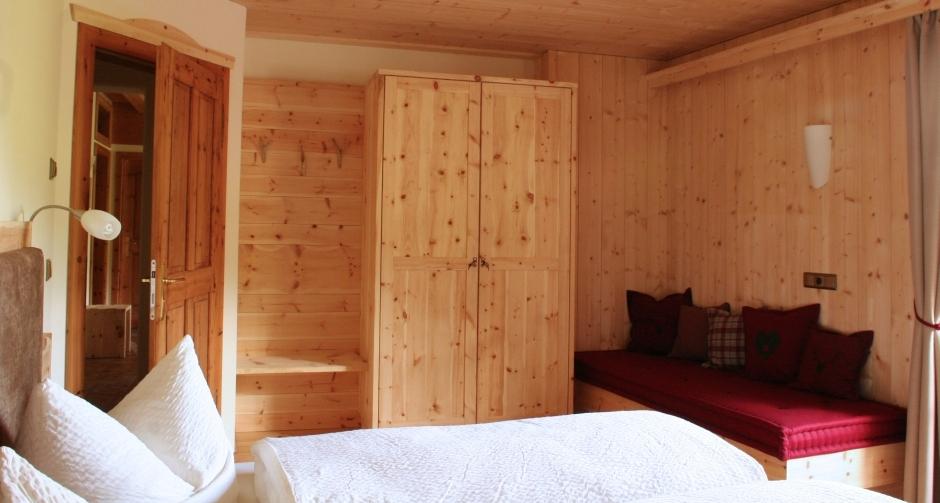 Schlafzimmer mit Vollholz-Zirmwand - Wohlgefühl und Holzduft